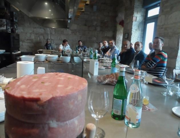 Előtérben a mangalicából készített mortadella, háttérben a bemutató résztvevői
